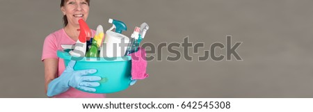 Smiling housewife holding a bucket with cleaning equipment