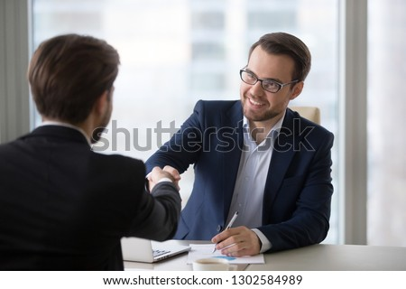 Smiling hr manager advisor insurer bank executive handshaking client applicant at meeting or job interview, satisfied businessmen shake hands thanking for good financial business deal, hiring concept