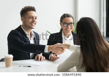 Smiling hr manager and hired female applicant won job interview shaking hands, friendly executive handshaking successful vacancy candidate offering employment contract, welcoming new worker concept