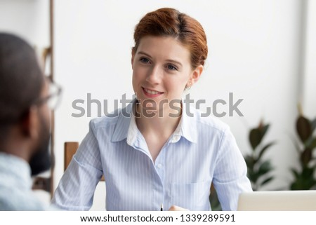 Smiling hr manager holding job interview with African American candidate in office, asking questions, employer attentively listening to applicant, good first impression, hiring process, close up