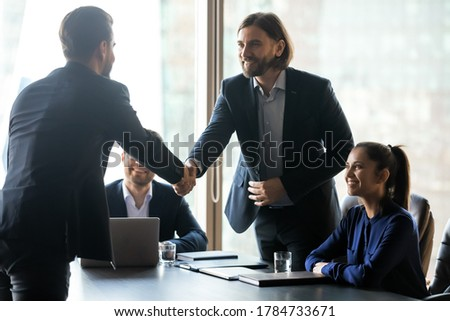 Smiling hr team leader shaking hands with job seeker, welcoming at interview, hiring process. Happy businessman greeting handshaking with partner client at group negotiations meeting in boardroom.