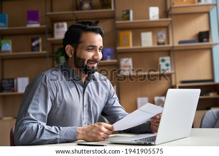 Smiling indian business man hr employer, teacher or lawyer holding cv document having virtual job interview meeting by video conference call, consulting client on laptop at online legal advice.