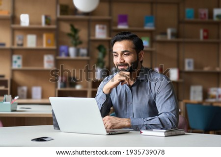 Smiling indian businessman working on laptop in modern office lobby space. Young indian student using computer remote studying, watching online webinar, zoom virtual training on video call meeting.