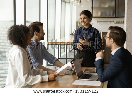 Smiling Indian businesswoman leading corporate meeting with diverse colleagues, coach mentor training employees, discussing project strategy, sharing ideas, business partners negotiation concept