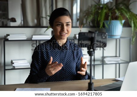 Smiling indian ethnic girl sitting in front of smartphone on stabilizer, recording self-presentation video or sharing professional skills. Happy young smart businesswoman filming educational lecture.