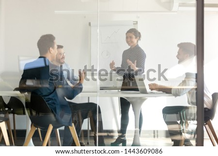 Smiling indian female presenter speaker give flip chart presentation in boardroom behind glass door, happy hindu business coach training diverse team talking to workers group at office workshop