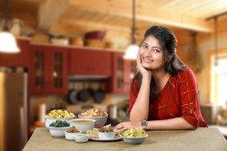 Smiling Indian girl or woman sitting in relax mood beside group of traditional Indian dishes and looking at the camera. Female model potrait