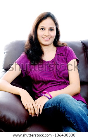 Smiling Indian girl sitting on Sofa against on white background ...