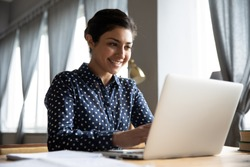 Smiling indian girl student professional employee typing on laptop sit at home office table, happy hindu woman studying e learning online software using technology app for work education concept