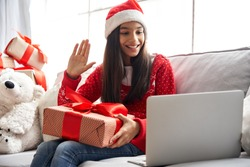 Smiling indian latin child kid girl wearing santa hat holding Christmas gift box, New Year present waving hand video calling family by webcam virtual meeting chat on holiday sitting on couch at home.