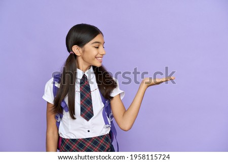 Smiling indian schoolgirl, preteen kid smiling looking at copy space holding hand. Advertising latin junior student standing isolated on violet lilac background. Education, school concept. Stock photo ©
