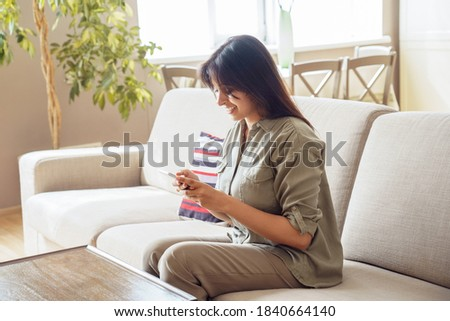 Smiling indian woman checking social media holding smartphone at home. Happy young lady using mobile online app, texting sms, chatting, playing game, shopping, orderring products on cell sit on couch. Stock fotó ©
