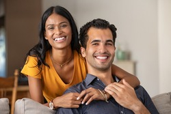 Smiling indian woman hugging her husband on the couch from behind at home. Loving middle eastern couple looking at camera with big grin. Portrait of laughing girl embracing handsome latin man on sofa.