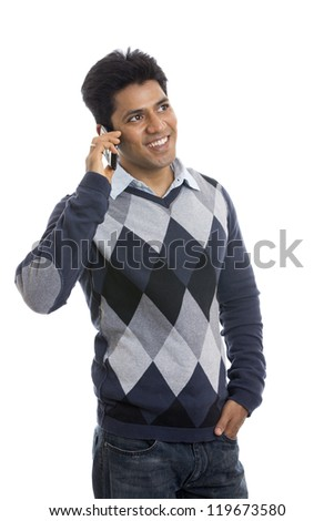 smiling Indian young man talking on the mobile phone  white background.