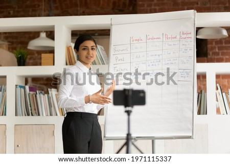 Smiling Indian young woman teacher recording flip chart presentation, webinar on smartphone, mentor coach explaining, holding online lesson, using phone webcam, e-learning and distance education