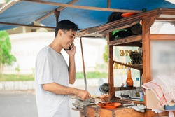 smiling indonesian sate ayam seller cooking the food while talking on a phone