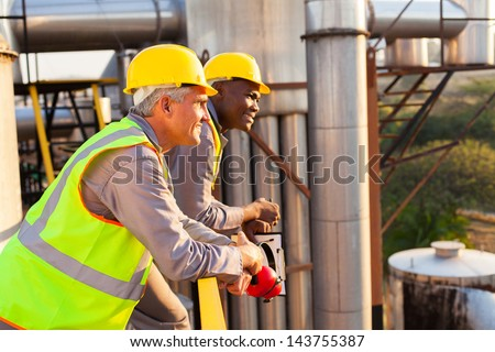 smiling industrial workers in safety gear