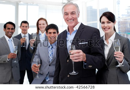 Smiling inernational business team holding glasses of Chamoagne to celebrate a success