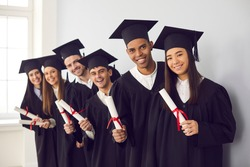 Smiling international students in traditional academic caps and gowns celebrating graduation. Group portrait of happy multiethnic college or university graduates holding diplomas and looking at camera