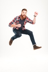 Smiling joyful man jumping and playing on invisible guitar isolated on a white background