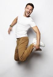 Smiling joyful man jumping on a white background.