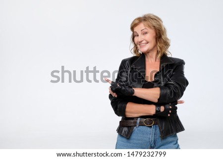 Smiling joyful mature woman in leather jacket pointing at copy space for advertisment or promotional text. Positive emotions, feelings, joy, happiness