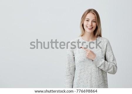 Smiling joyful woman with blonde dyed hair in loose sweater posing against gray studio wall pointing at copy space for advertisment or promotional text. Positive emotions, feelings, joy, happiness