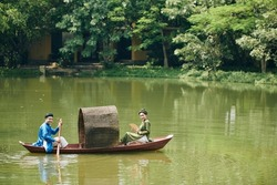 Smiling just married Vietnamese couple in traditional dresses and headwear rowing boat in small pond