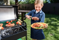 smiling kid boy in apron preparing tasty stakes on barbecue grill outdoors