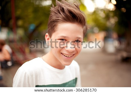 Smiling kid boy with stylish hairstyle outdoors. Looking at camera. Teenage boy