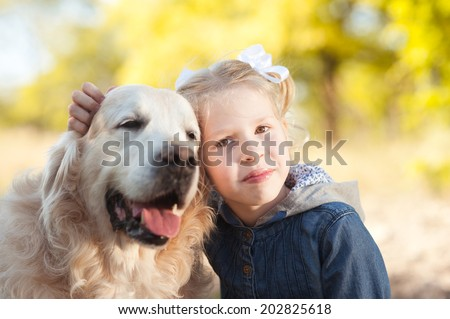 Smiling kid girl with dog outdoors
