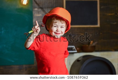 Smiling kid holding spanner and pointing up with his finger. Cute boy having fun in workshop. Little builder wearing protective helmet