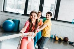 Smiling kids in sportswear pulling rope in gym