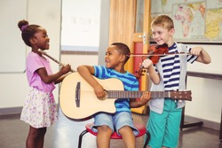Smiling kids playing guitar, violin, flute in classroom at school