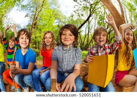 Smiling kids reading a book in the summer forest #520051651