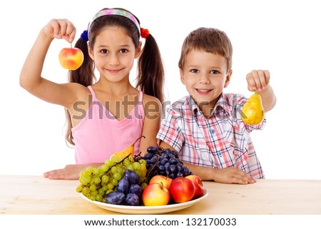 Smiling kids with apple and pear in hands and plate of fruits on the table, isolated on white, isolated on white