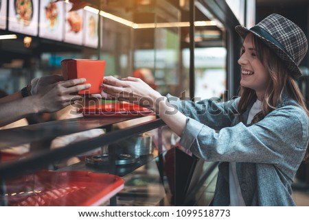 Smiling lady is receiving order in oriental restaurant. She is looking with joy at cafe worker giving her food box