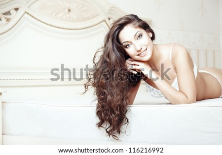 Smiling lady lying and pamepring in bedroom