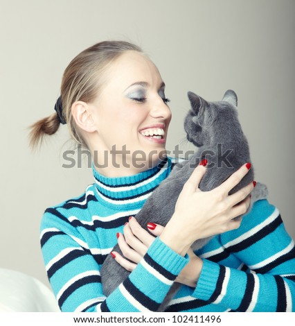 Smiling lady plays with cat indoors