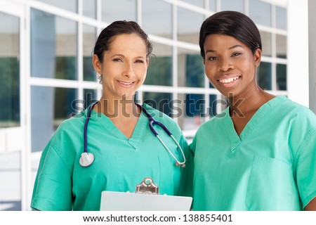 Smiling latin and afro-american nurse holding a clipboard in brightly lit exterior hospital environment in scrubs, white lab coat and holding glasses.