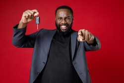 Smiling laughing young african american business man 20s wearing classic jacket suit standing pointing index finger on camera hold car keys isolated on bright red color background studio portrait