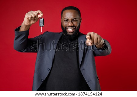 Smiling laughing young african american business man 20s wearing classic jacket suit standing pointing index finger on camera hold car keys isolated on bright red color background studio portrait ストックフォト ©
