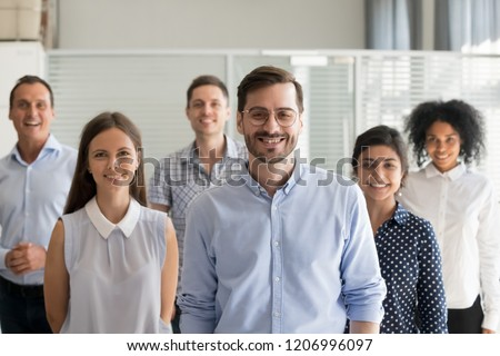 Smiling leader ceo or professional business coach looking at camera posing in office with diverse happy team at background, successful startup founder, corporate employee with staff members portrait
