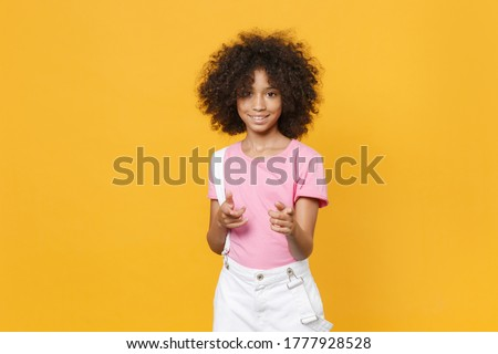Smiling little african american kid girl 12-13 years old in pink t-shirt isolated on yellow background studio portrait. Childhood lifestyle concept. Mock up copy space. Point index fingers on camera Foto d'archivio ©