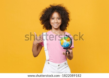 Smiling little african american kid girl 12-13 years old in pink t-shirt isolated on yellow wall background. Childhood lifestyle concept. Mock up copy space. Hold Earth world globe showing thumb up Foto stock ©