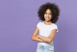 Smiling little african american kid girl 12-13 years old in white t-shirt isolated on pastel violet background studio portrait. Childhood lifestyle concept. Mock up copy space. Holding hands crossed