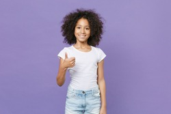 Smiling little african american kid girl 12-13 years old in white t-shirt isolated on pastel violet wall background studio portrait. Childhood lifestyle concept. Mock up copy space. Showing thumb up