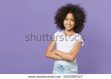 Smiling little african american kid girl 12-13 years old in white t-shirt isolated on pastel violet background studio portrait. Childhood lifestyle concept. Mock up copy space. Holding hands crossed Stock photo ©