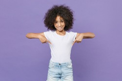 Smiling little african american kid girl 12-13 years old in white t-shirt isolated on violet background studio portrait. Childhood lifestyle concept. Mock up copy space. Pointing index fingers down