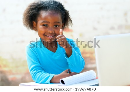 Smiling little African student doing thumbs up sigh at desk. Stock photo ©